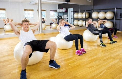 Bosu toplarının üzerinde egzersiz yapan insanlar.
