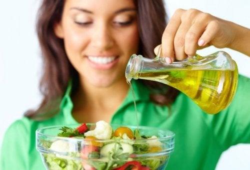salataya zeytinyağı koyan kadın