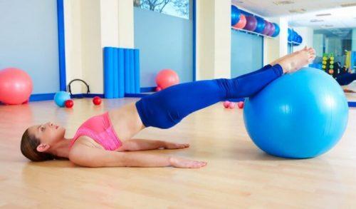 kadın pilates topu ile spor yapıyor
