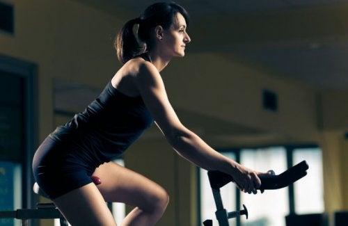 Sabit bisiklet üzerinde egzersiz yapan bir kadın.