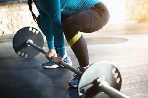 Halter kaldırmaya çalışan bir kadın sporcu.
