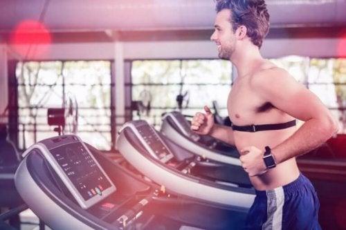 Kalp ritim hızı ölçen bir kol saati takan ve koşu bandında koşu egzersizi yapan bir adam.