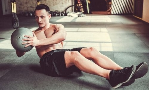 Sağlık topu ile karın egzersizi yapan bir adam.