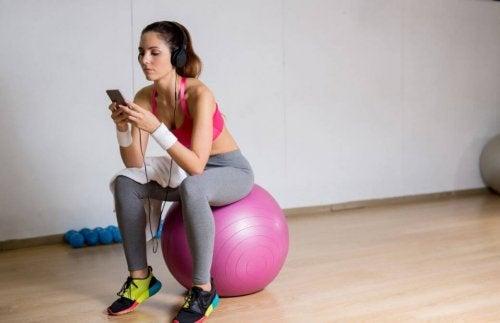 Pilates topunun üzerine oturmuş telefonuna bakan kadın.