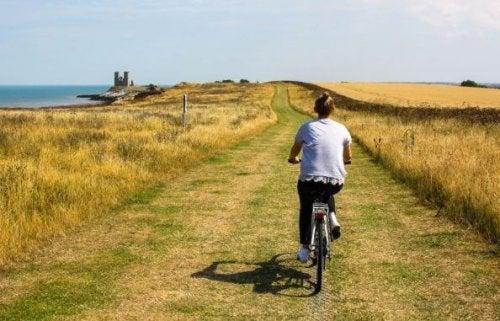 Doğal bir ortamda bisiklet yolculuğuna çıkmış bir kadın.