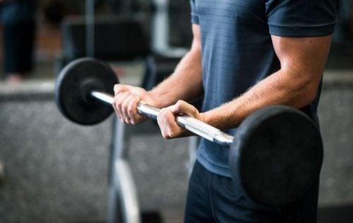 Fitness barı ile ön kol egzersizi yapan bir adam