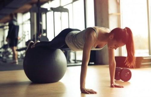 denge topu ile pilates yapan kadın