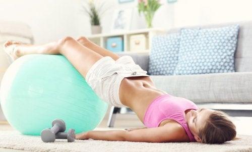 Sağlık topu ile kalça kaldırma egzersizi yapan kadın