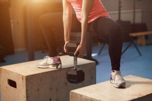 Dambıl ile squat egzersizi yapan kadın
