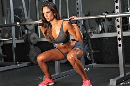 Ağırlıklarla squat egzersizi yapan bir kadın.
