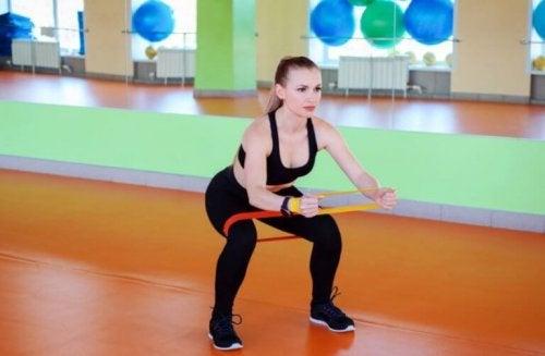 Mini bir bant kullanarak squat yapan bir kadın.