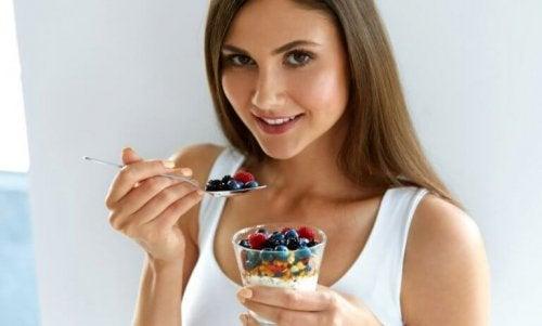 Taze meyveli yulaf lapası yiyen kadın