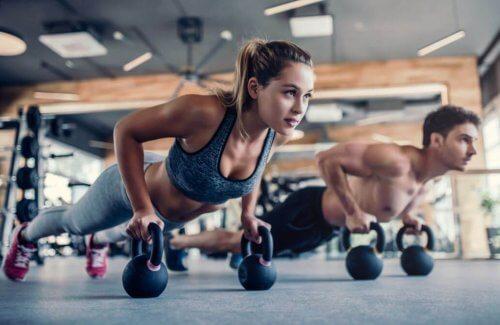 Dambıl ile biseps egzersizleri yapan kadın ve adam