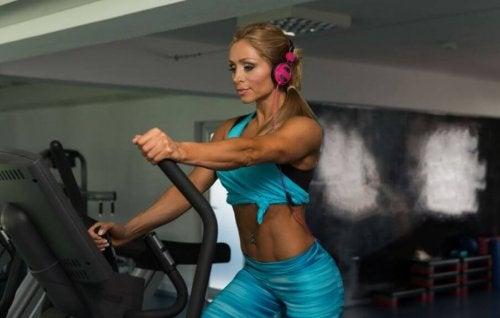 Eliptik makinesi ile egzersiz yapan kadın.
