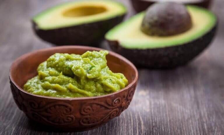 ikiye bölünmüş avokado ve bir kase guacamole