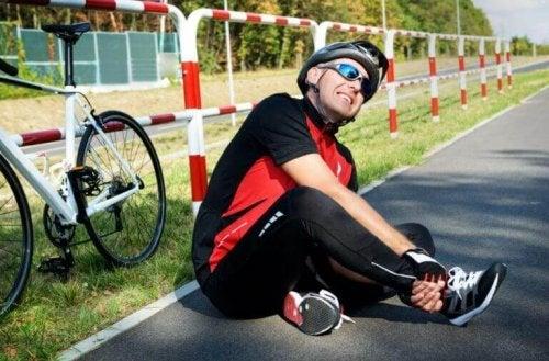 ayağı sakatlanmış bisikletin yanında oturan adam
