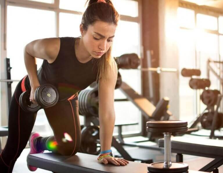 dambıl row egzersizi yapan kadın