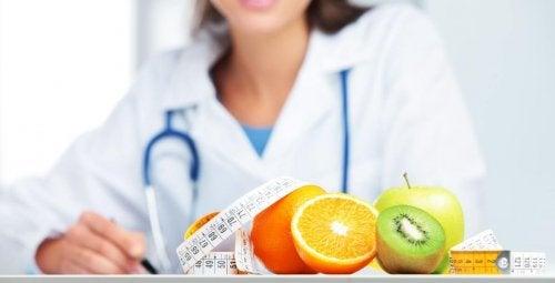 diyetisyen kadın, taze meyveler ve mezura