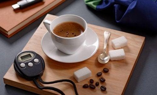 bir fincan kahve, tansiyon ölçme aleti ve küp şekerler