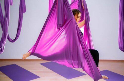 mor kumaşlarla hava yogası yapan kadın