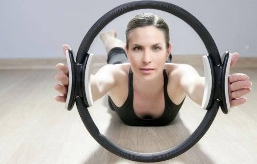 pilates çemberi ile egzersiz yapan kadın