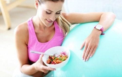 egzersiz rutini sonrası yemek yiyen kadın