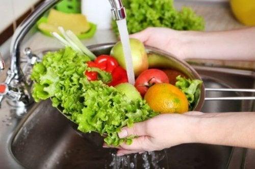 lavaboda meyve ve sebze yıkayan kadın