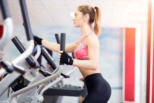 eliptik bisiklet ile egzersiz yapan kadın