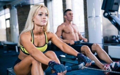 spor salonunda kürek makinelerinde çalışan insanlar