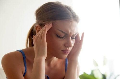 kas gerilimi nedeniyle başı ağrıyan kadın