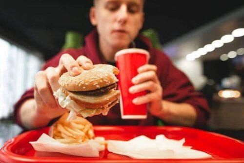 hamburger ve patates kızartması yiyen adam