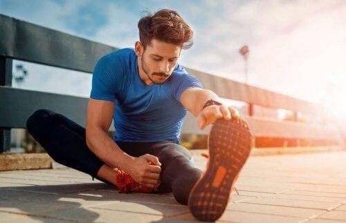 spordan sonra yerde bacak germe hareketi yapan adam