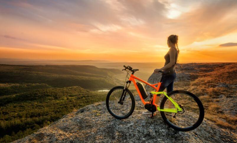 Bisikleti ile bir tepede duran kadın