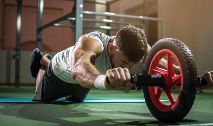 Karın egzersiz tekerleği ile vücut çalışan bir adam