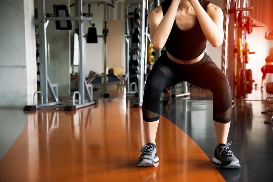 Spor salonunda squat yaparak üst bacak incelten kadın
