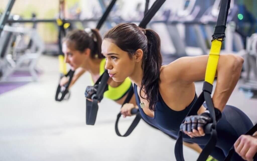 TRX bantları ile chest press egzersizi yapan kadın