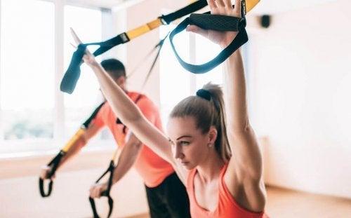 TRX bantları ile egzersiz yapan kadın