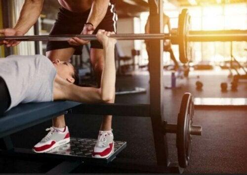 Spor salonunda ağırsiklet antrenmanı yapan çift