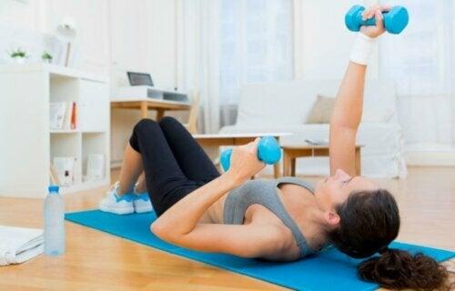 evde dambıllarla egzersiz yapan kadın