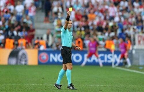 sarı kart gösteren futbol maçı hakemi