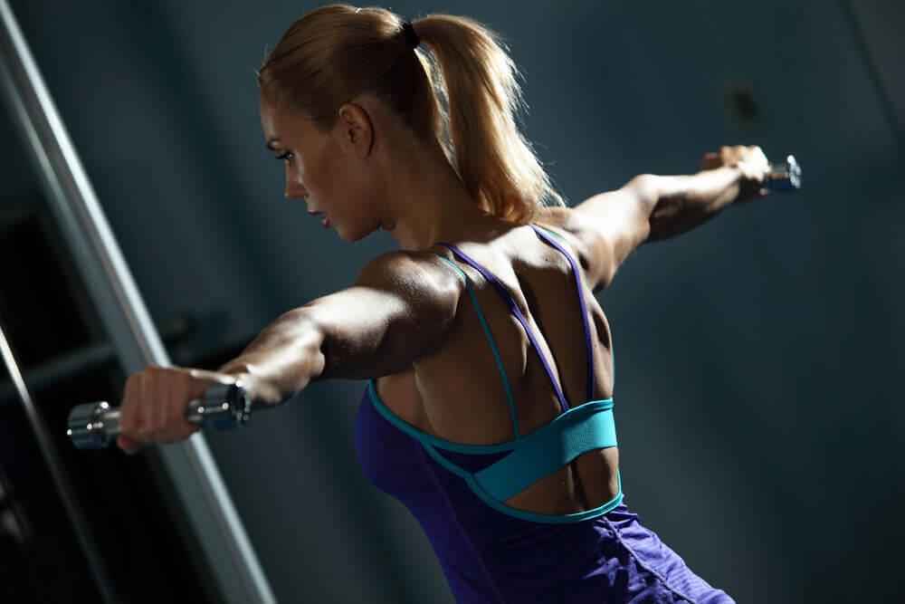Ağırlık ile kolları iki yana kaldırma egzersizi yapan kadın