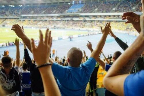 maç izlerken elleri havada ayakta duran seyirciler
