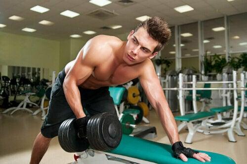 Yüksek ağırlıklı dambıl kullanarak kas yetmezliği egzersizi yapan bir adam.