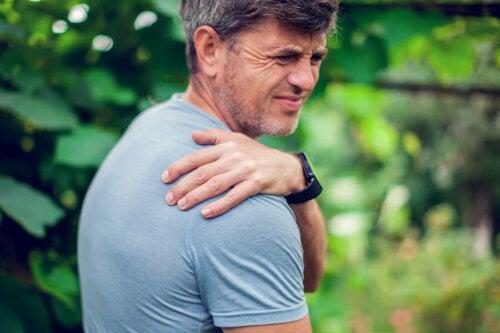 Açık havada boyun veya omuz ağrısı çeken koyu saçlı mutsuz adam.