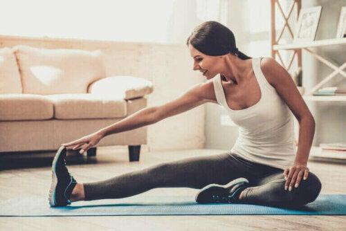 evde mat üstünde ısınma hareketleri yapan mutlu kadın