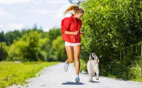 parkta golden cins köpeği ile koşan kırmızılı kadın