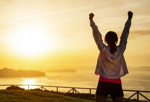 gün batımı kollarını havaya kaldıran kadın spor