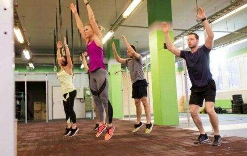 spor salonunda burpee hareketinin zıplama bölümünde olan sporcular