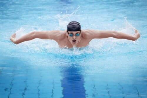 Bir adam havuzda kelebek stilinde yüzüyor