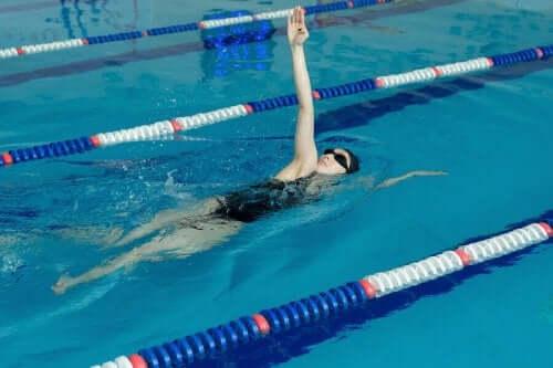Bir kadın havuzda sırtüstü yüzüyor